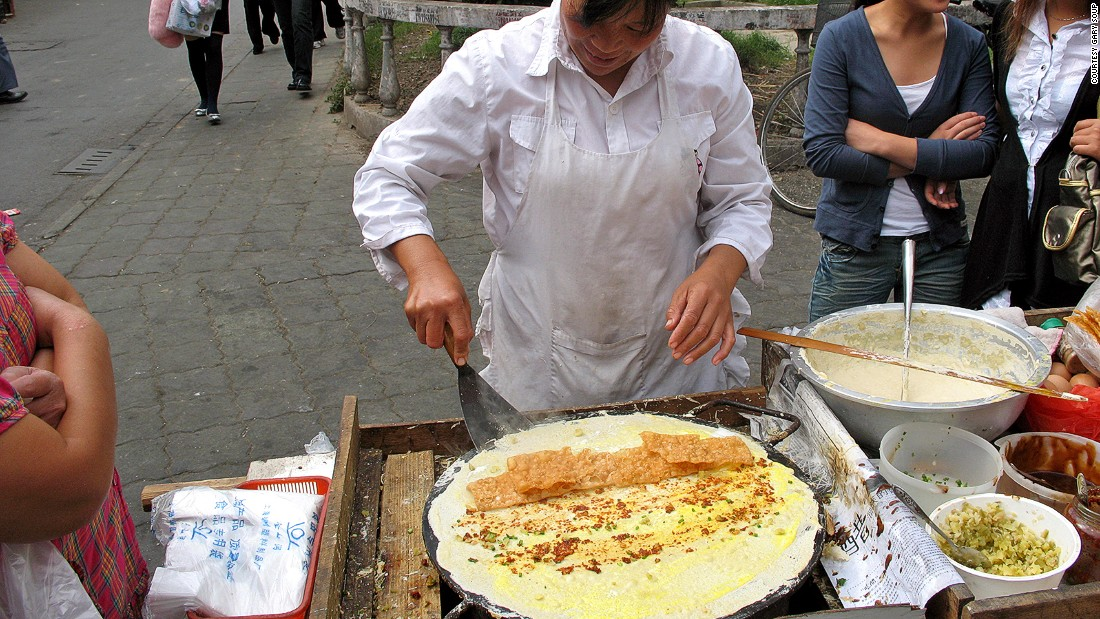 Street chefs ladle batter on a hot pan, swirl it into a perfect circle, then break an egg on top. They can fill the center with anything from deep-fried dough and ham sausages to sweet paste and chili sauce with coriander.
