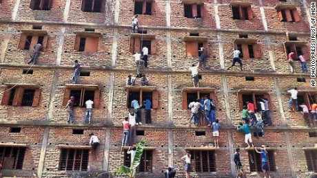In this Wednesday, March 18, 2015 photo, parents climb the wall of a building to help students appearing in an examination in Hajipur, in the eastern Indian state of Bihar.
