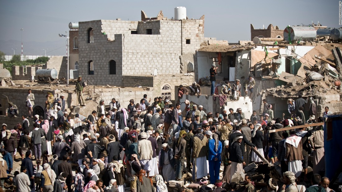People search for survivors under the rubble of houses destroyed by airstrikes near the Sanaa Airport on March 26.