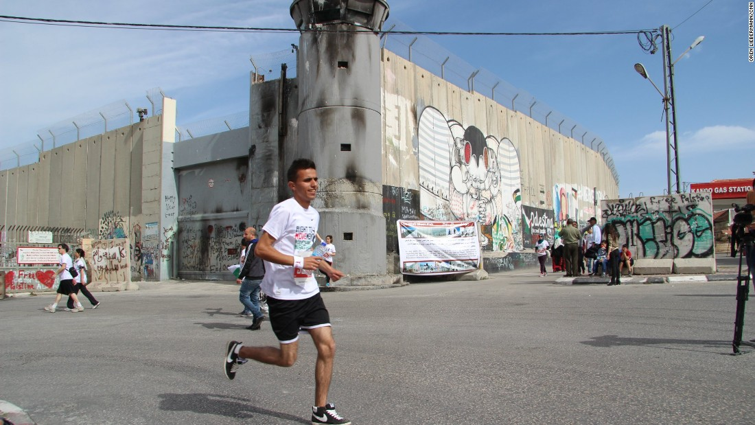 A runner passes Israel's separation barrier in Bethlehem, West Bank, as he participates in the Palestine Marathon on Friday, March 27.