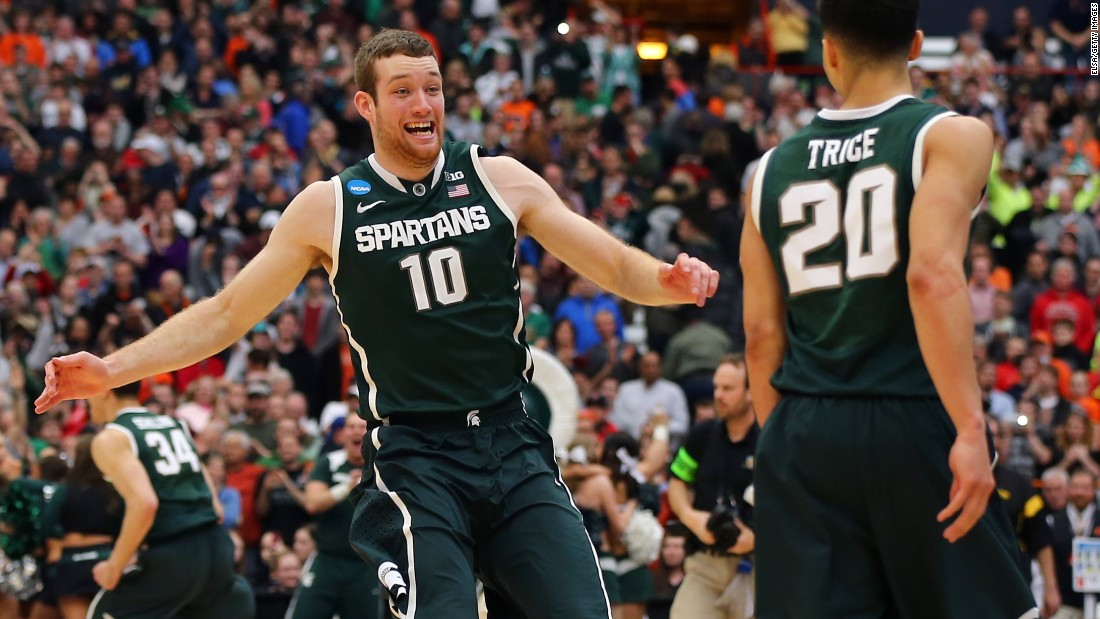 Matt Costello (10) and Travis Trice (20) of the Michigan State Spartans celebrate defeating the Louisville Cardinals 76 to 70 in overtime of the East Regional Final of the 2015 NCAA Men's Basketball Tournament at Carrier Dome on March 29, 2015 in Syracuse, New York.
