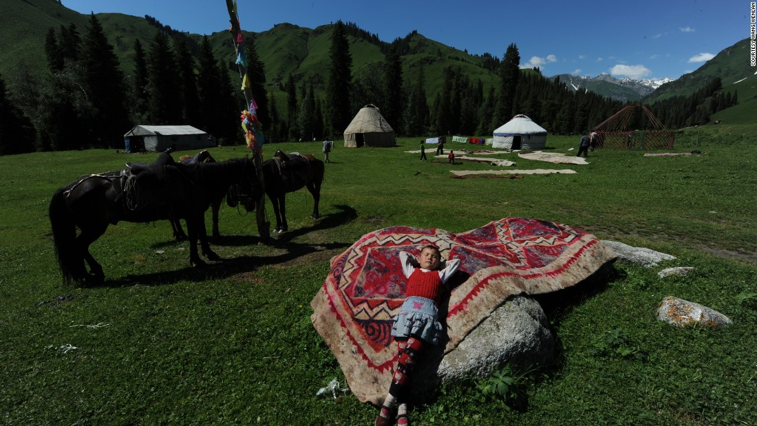 A boy from a nomadic family leans on a rug in 2010 near Ili, Xinjiang.