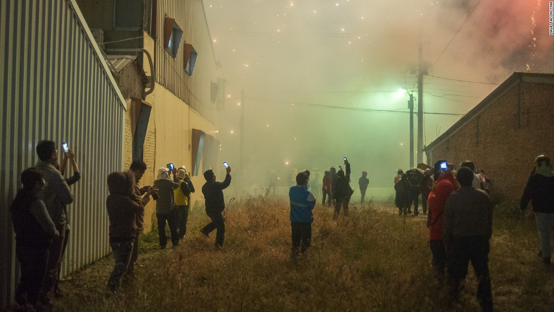 Not everyone wants to stand in the middle of the action. These attendees -- wreathed in sulfur fumes -- watch the fireworks from the safety of a vacant lot.