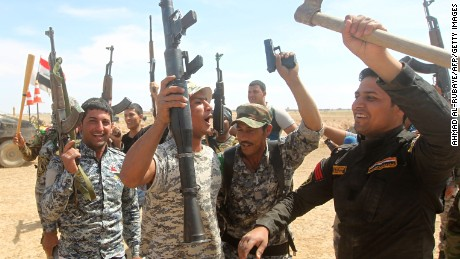 Iraqi government forces raise their weapons as they hold a position on the western outskirts of Tikrit, on March 27, 2015, during a military operation to retake the city from Islamic State group jihadists. Iraqi government forces revived a stalled ground operation to retake Tikrit on March 26, 2015, following US-led air strikes that paved the way but left the anti-jihadist camp deeply divided. AFP PHOTO / AHMAD AL-RUBAYE (Photo credit should read AHMAD AL-RUBAYE/AFP/Getty Images)