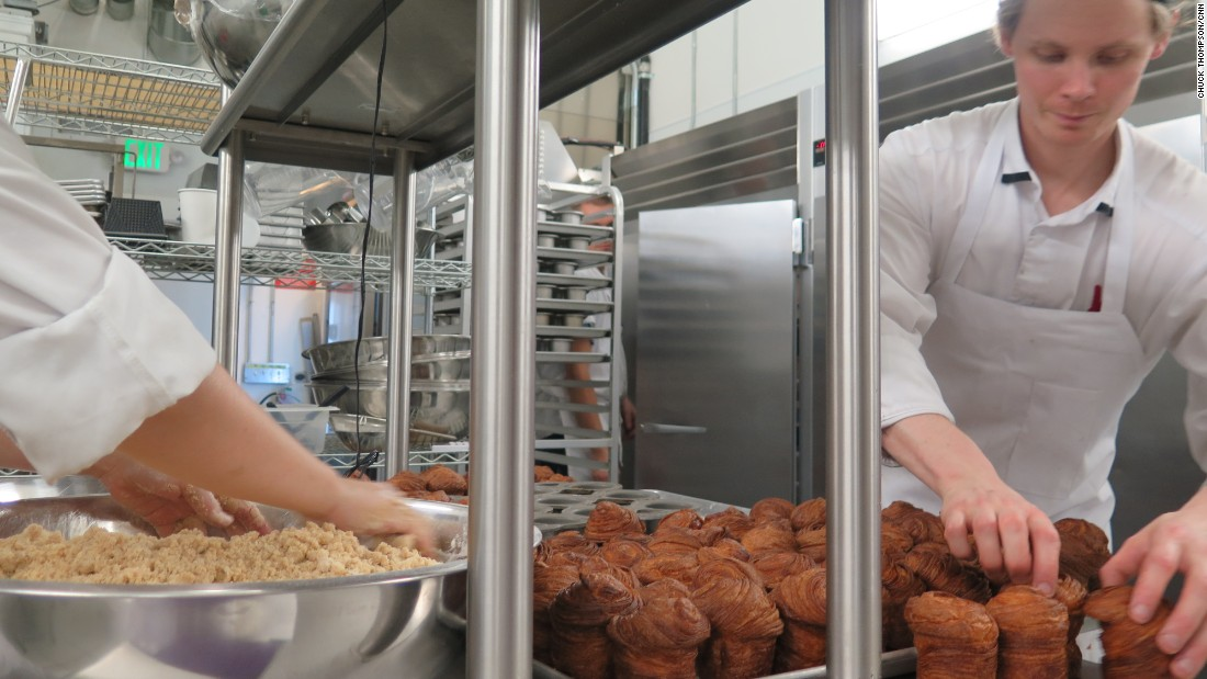 Mr. Holmes Bakehouse pastry chef and co-owner Ry Stephen (right) wrangles cruffins fresh from the oven. They'll be dusted with sugar in a moment then sold to customers lined up outside.