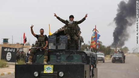 Iraqi security forces celebrate as they a street in Tikrit, on April 1, 2015, a day after the prime minister declared victory in the weeks-long battle to retake the city from the Islamic State (IS) group. Iraqi forces battled the last jihadists in the northern city on April 1, 2015 to seal a victory the government described as a milestone in efforts to rid the country of the Islamic State group. AFP PHOTO / AHMAD AL-RUBAYE        (Photo credit should read AHMAD AL-RUBAYE/AFP/Getty Images)