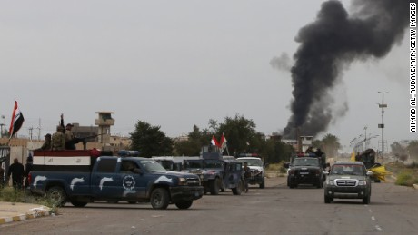 Smoke rises from buildings as Iraqi security forces patrol a street in Tikrit, on April 1, 2015, a day after the prime minister declared victory in the weeks-long battle to retake the city from the Islamic State (IS) group
