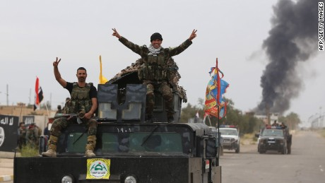 Iraqi security forces celebrate as they a street in Tikrit, on April 1, 2015, a day after the prime minister declared victory in the weeks-long battle to retake the city from the Islamic State (IS) group. Iraqi forces battled the last jihadists in the northern city on April 1, 2015 to seal a victory the government described as a milestone in efforts to rid the country of the Islamic State group. AFP PHOTO / AHMAD AL-RUBAYEAHMAD AL-RUBAYE/AFP/Getty Images