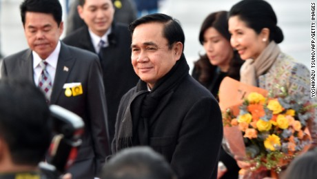 Thai Prime Minister Prayut Chan-O-Cha (C), accompanied by his wife Naraporn (R), arrives at Tokyo International Airport on February 8, 2015.