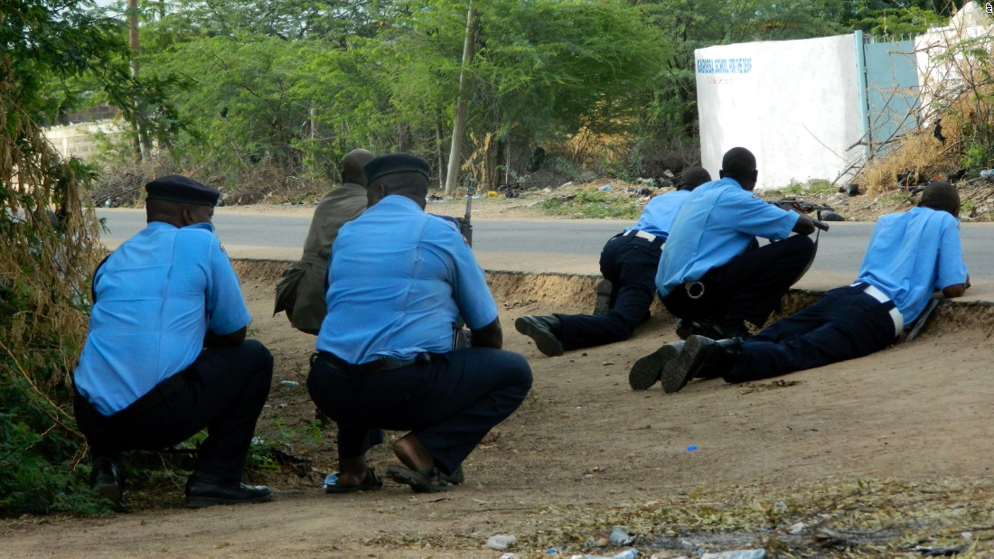 Kenyan police take cover outside the school during the attack.