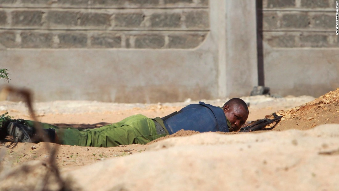 A Kenyan soldier takes cover as shots are fired in front of the school on April 2, 2015.