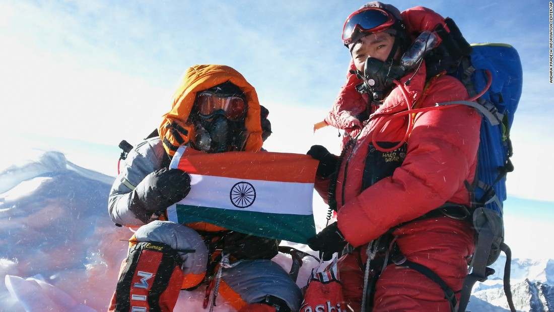 Malavath Poorna, left, holds up her national flag on May 24, when the 13-year-old daughter of poor Indian farmers became the youngest girl to climb Everest.
