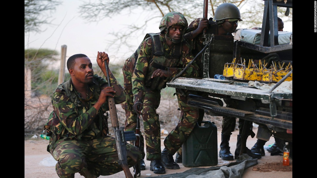 Kenyan soldiers take cover as heavy gunfire continues in front of the school on April 2, 2015.