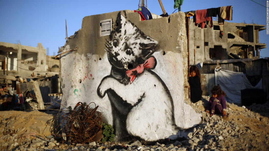 A Palestinian child stands next to a Banksy mural of a kitten on the remains of a destroyed house in Beit Hanoun, Gaza, in February 2015.