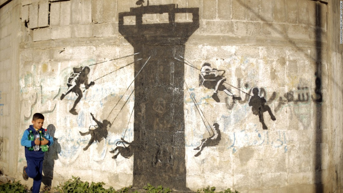 In February 2015, the secretive street artist was in Beit Hanoun, Gaza. His mural, here, depicts children using an Israeli army watchtower as a swing ride.