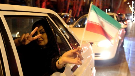 "A woman in a car flashes the ""V for Victory"" sign and waves an Iranian flag as people celebrate on Valiasr street in northern Tehran on April 2, 2015, after the announcement of an agreement on Iran nuclear talks. Iran and global powers sealed a deal on April 2 on plans to curb Tehran's chances for getting a nuclear bomb, laying the ground for a new relationship between the Islamic republic and the West. AFP PHOTO / ATTA KENAREATTA KENARE/AFP/Getty Images"