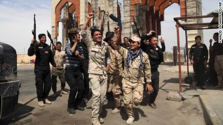 Iraqi security forces chant slogans against ISIS in Tikrit, Iraq, after reopening the main gate of their base, that was closed for months while ISIS occupied the town.