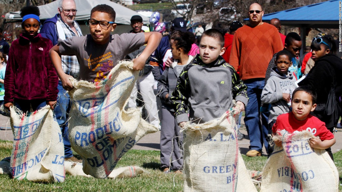 Roman Taliafero, second from left, leads the sack race against Danny McCleary and Cayten McCleary, right, during an April 4 Easter egg hunt  sponsored by People Uniting Neighbors and Churches, at Cork Hill Park in Davenport, Iowa.