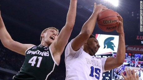 :INDIANAPOLIS, IN - APRIL 04: Jahlil Okafor #15 of the Duke Blue Devils handles the ball against Colby Wollenman #41 of the Michigan State Spartans in the first half during the NCAA Men's Final Four Semifinal at Lucas Oil Stadium on April 4, 2015 in Indianapolis, Indiana. (Photo by Andy Lyons/Getty Images)