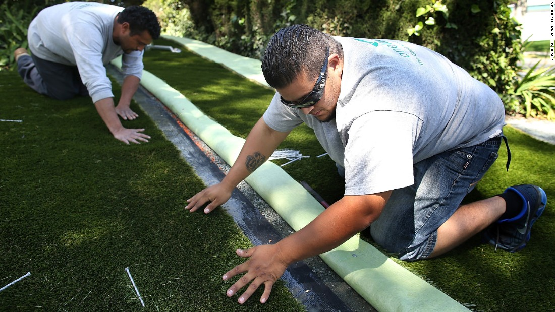 Workers install artificial grass at a home in Burlingame, California, in April.