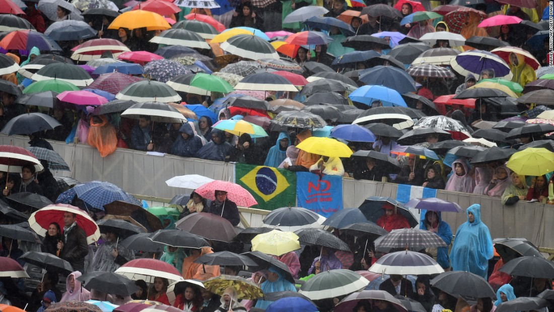 Worshippers hold umbrellas under heavy rain during the Easter Mass at St. Peter's Square in the Vatican on April 5.