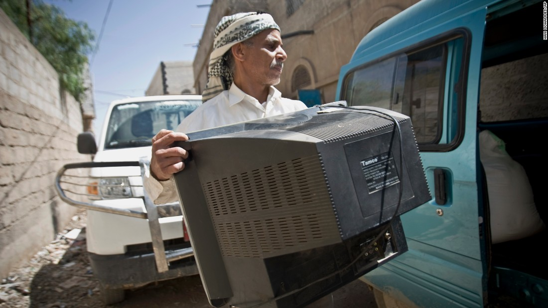 A Yemeni man loads a TV set into a van as he prepares to flee Sanaa on Thursday, April 2.
