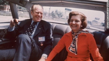 United States President Gerald Ford and wife Betty Ford sitting in the back seat of a car smiling and holding hands in 1975.