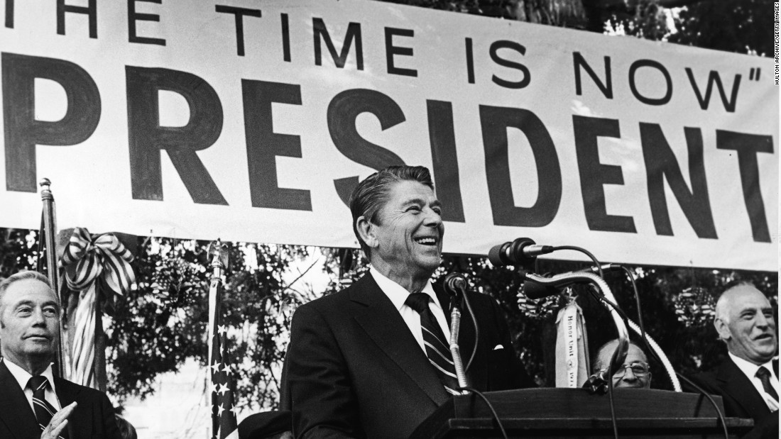 "Reagan smiles as he speaks about his presidential campaign in 1979 front of a large banner with his campaign slogan, ""The Time is Now."""