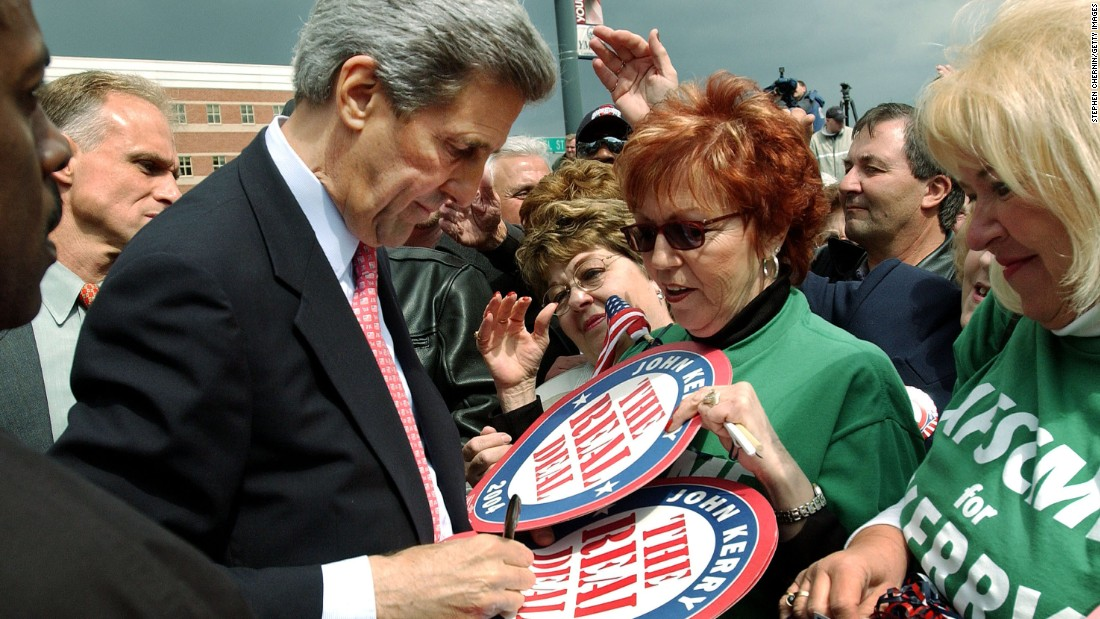 "John Kerry signs ""The Real Deal"" campaign posters for supporters after a rally on April 27, 2004, in Youngstown, Ohio."