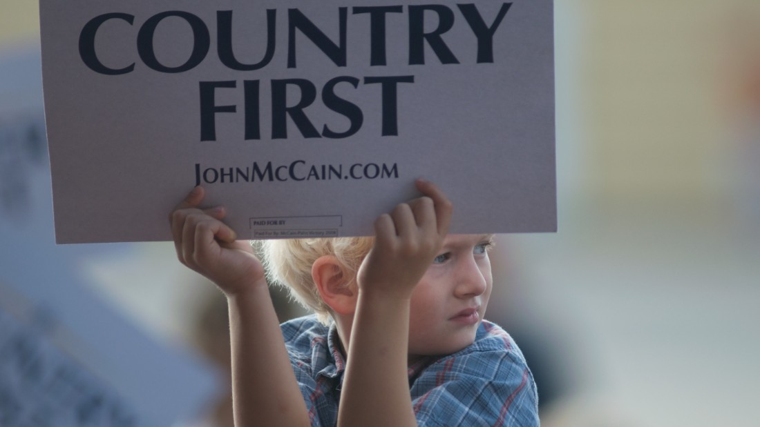 "A child holds up a ""Country First"" sign while waiting for vice presidential candidate Alaska Gov. Sarah Palin and presidential nominee Sen. John McCain at a rally of supporters on September 18, 2008, in Cedar Rapids, Iowa."