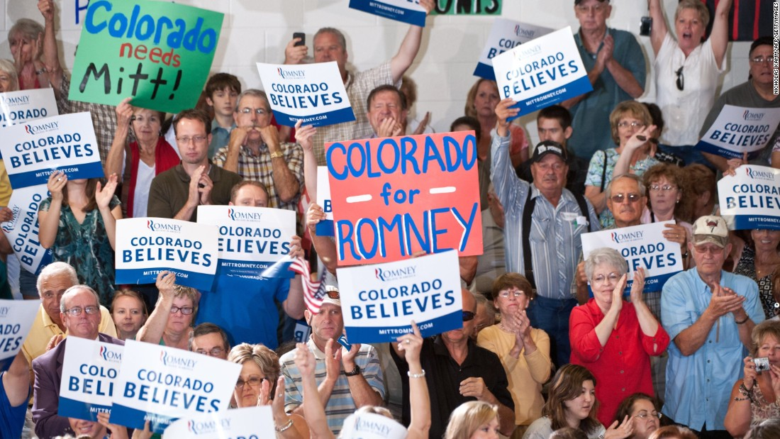 "People cheer as Republican presidential candidate Mitt Romney speaks at a town hall meeting in Grand Junction, Colorado, on July 10, 2012. Supporters hold up ""Colorado Believes"" signs, based on Romney's ""Believe in America"" campaign slogan."