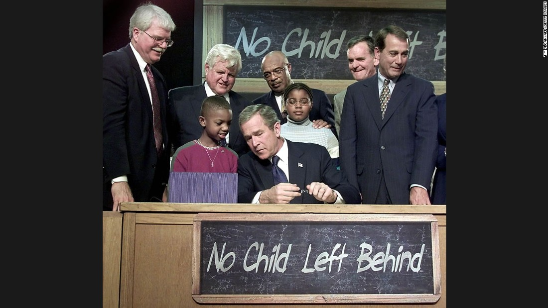 "President George W. Bush waves from the stage during a bill-signing ceremony for the No Child Left Behind Act during a visit to Hamilton High School in Hamilton, Ohio, on January 8, 2002. ""Leave No Child Behind"" was a popular slogan during Bush's presidential campaign."