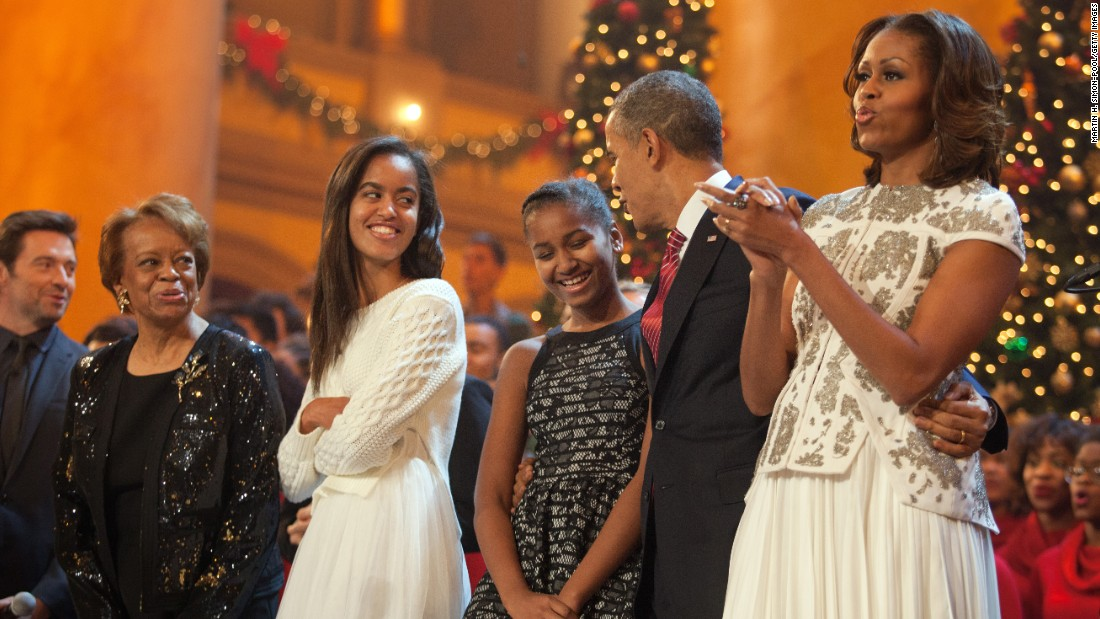 "The first family sings during the finale of TNT's ""Christmas in Washington"" program in December 2013. Michelle Obama's mother, Marian Robinson, and the program's host, actor Hugh Jackman, are at left. Time Warner is the parent company of TNT and CNN."