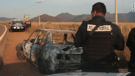Federal police stand next to a bullet riddled and burned car after a criminal gang ambushed a police convoy near the town of Soyatlan, near Puerto Vallarta, Mexico, Monday, April 6, 2015. According to the Jalisco state prosecutors office, at least 15 state policed officers were killed and five others wounded, the single deadliest attack on Mexican police in recent memory.