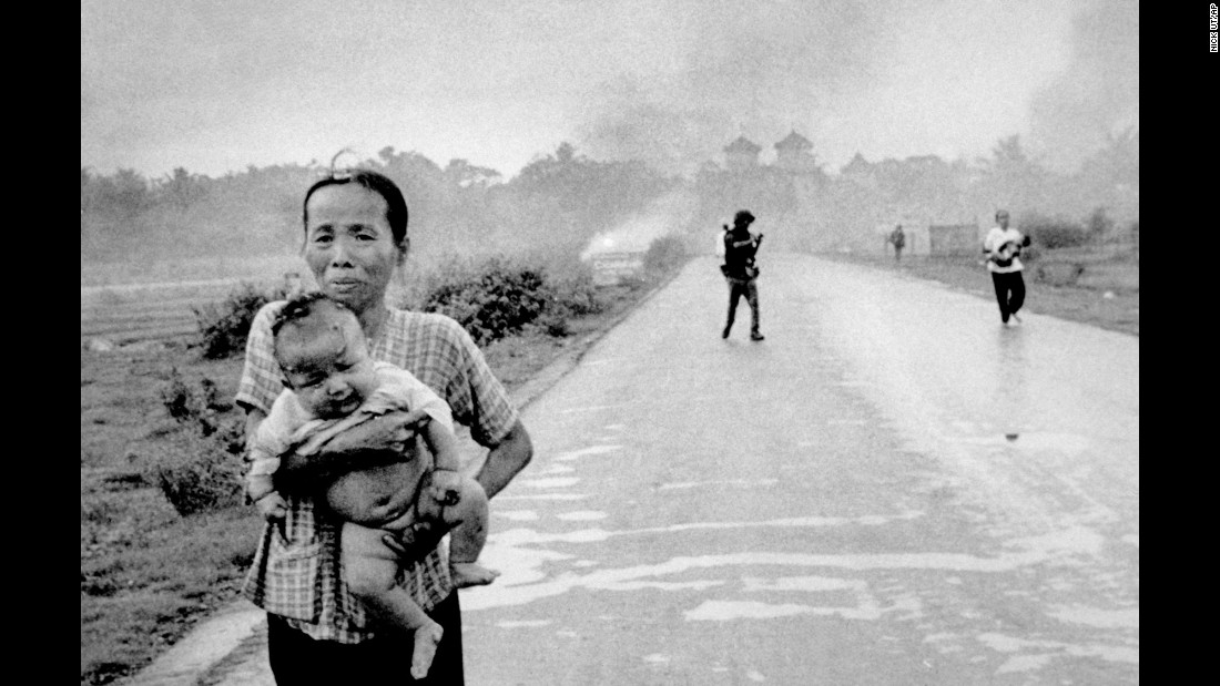 Women carry severely burned children down the road after the attack.