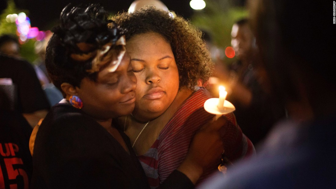 Chasyn Carter, right, embraces Candice Ancrum during a candlelight vigil outside North Charleston's City Hall on Wednesday, April 8.