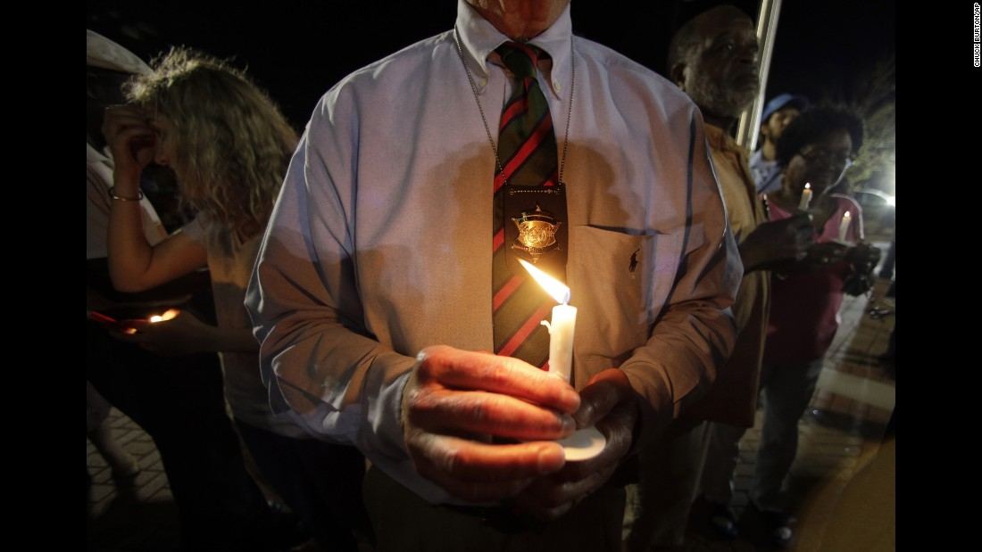 Charleston County Sheriff Al Cannon holds a candle as he joins the City Hall protest on April 8.