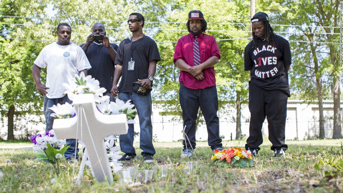 Darrell Mikell, Aaron Moses, Justin Lewis and Quin Dalton stand April 8 near the site where Scott was shot and killed. The person in the background is unidentified.