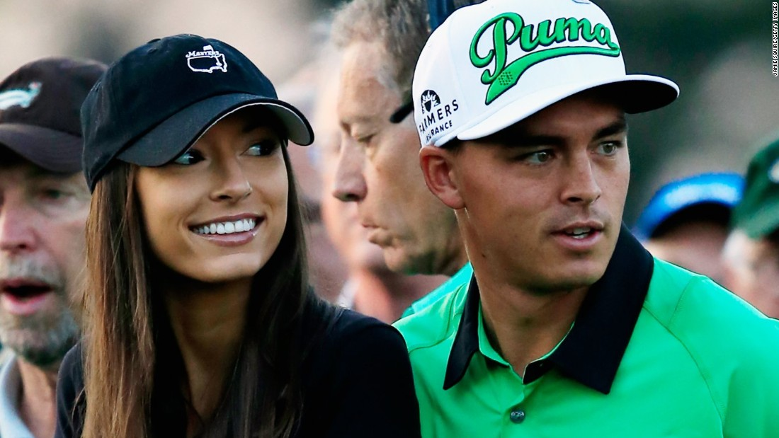 American Rickie Fowler, who tied for fifth at last year's Masters, waits for his tee-off with girlfriend Alexis Randock. The Ryder Cup player ended the opening day tied for 41st on 73 with Woods.