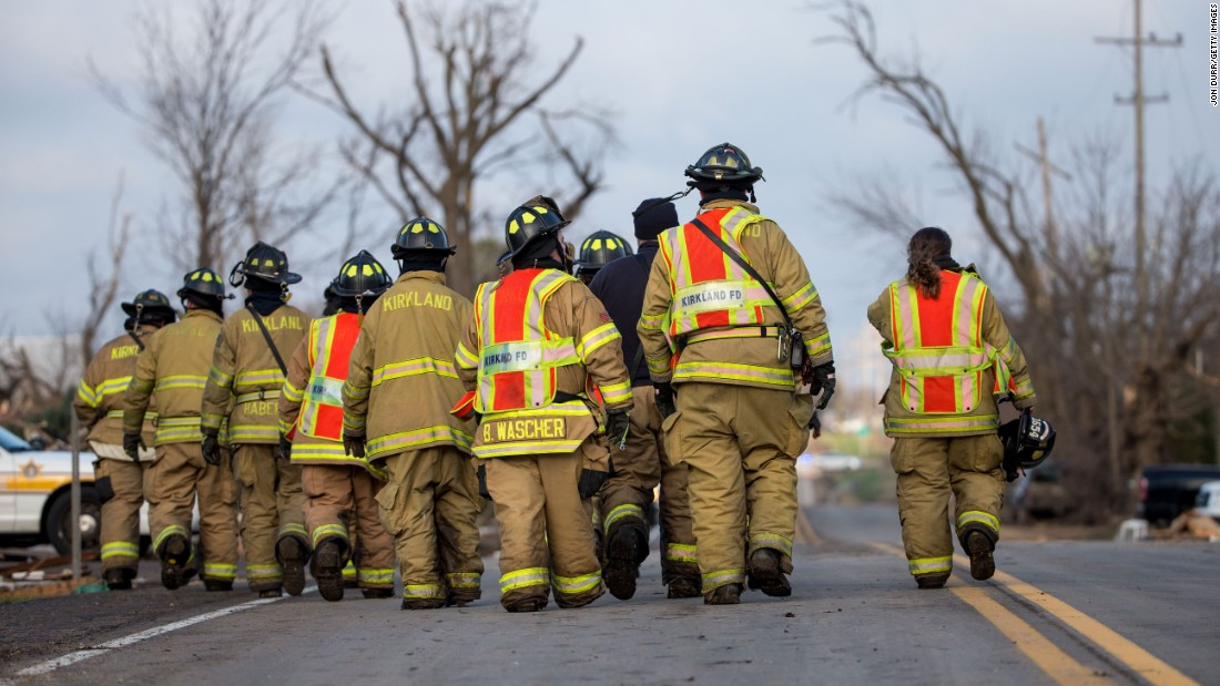 The Kirkland Fire Department walks along a highway while searching for unaccounted people in Fairdale on April 10.