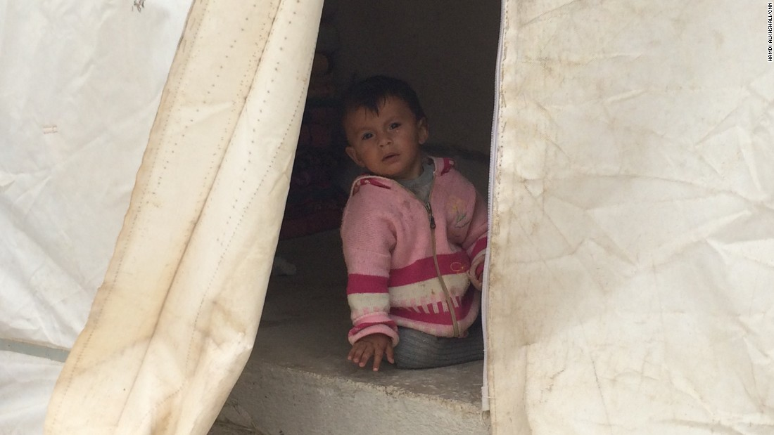 A small child is seen within the safety of a tent at the refugee camp. It's not known how long they'll have to stay here.