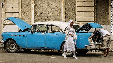 A woman walks past a vintage American car on December 31, 2013, in Havana. A new regulation released by Cuban President Raul Castro will allow Cubans or foreign residents to freely buy new or used cars in government-run stores as of January 3, 2014; after 50 years of automobile sales regulations.