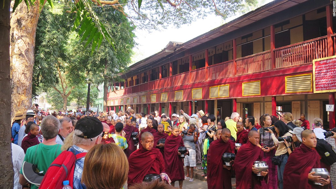 Around 10 a.m. each day, tourists gather on the side of the road at Mahagandhayon Monastic Institution in Amarapura, Myanmar, waiting for the appearance of the monastery's monks.