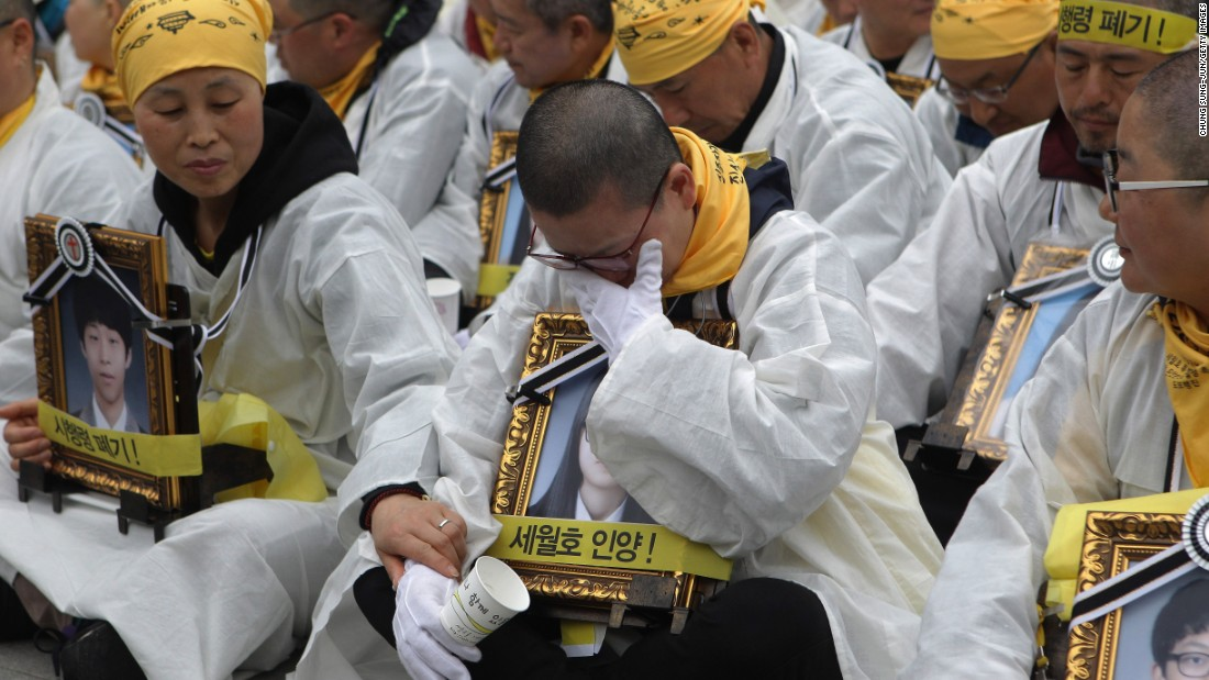 Relatives of victims of the Sewol ferry hold portraits of victims during a rally on April 5, 2015 in Seoul. Relatives, students and citizens attended the vigil to pay tribute to the victims of the ferry disaster and demanded that the wreckage be salvaged.