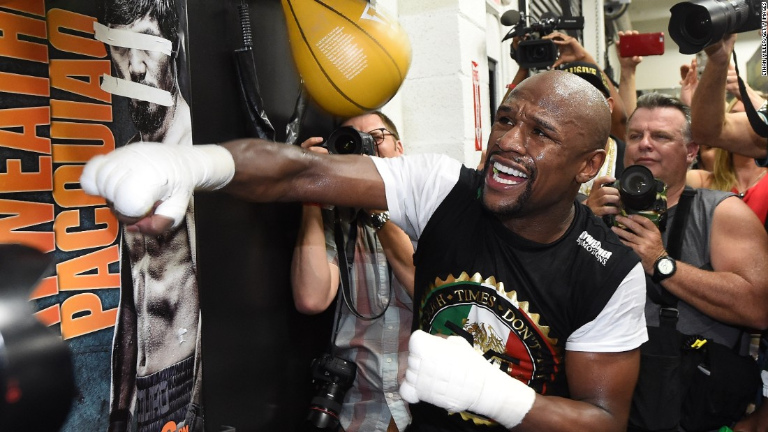 Showing off in front of the reporters, Mayweather pummels a speed bag. Look closely, and you'll see a poster of Pacquiao with his eyes and mouth taped over.