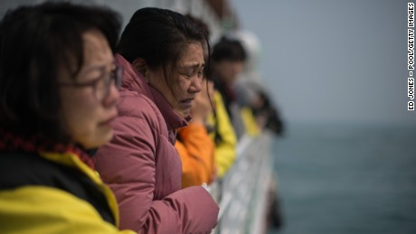A relative of victims of the Sewol ferry disaster weeps as she and others stand on the deck of a boat during a visit to the site of the sunken ferry on April 15, 2015 in Jindo-gun, South Korea.