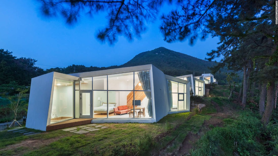 Designed by Atelier Chang, Knot House is made up of five white, sculptural buildings that rest on a cliff on the southern coast of Geoje Island. The white walls fold in on themselves to create a private ocean view from each house.