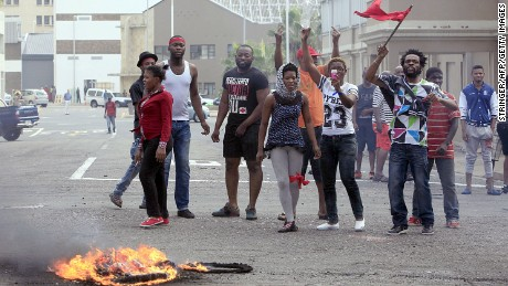Foreign nationals gesture after clashes break out between a group of locals and police in Durban on April 14, 2015 in ongoing violence against foreign nationals in Durban.