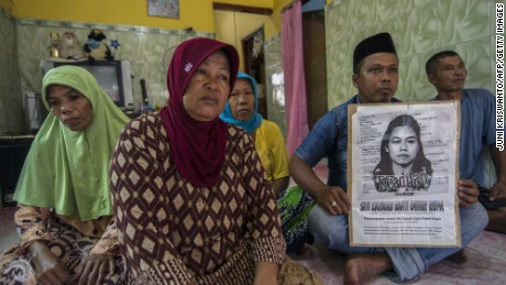 Family members of beheaded Indonesian maid Siti Zainab hold her portrait at their family home in Bangkalan, East Java province on April 15, 2015.