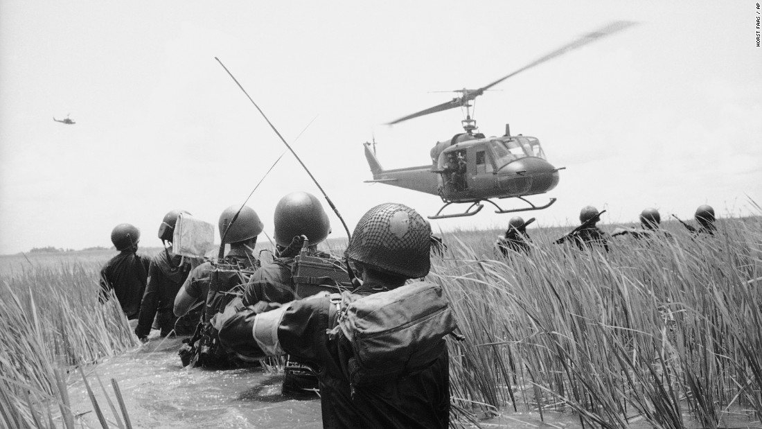 A South Vietnamese reconnaissance unit walks hip-deep in water as a U.S. helicopter skims over reeds in the Mekong Delta in October 1964. They were on the lookout for Viet Cong guerrillas.